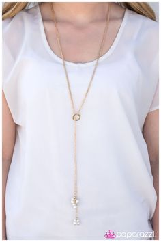Clusters of dainty white pearls dangle from the bottom of an elongated gold chain. Infused with a bold gold circle, the elongated gold chain loops through the circle creating an elegant lariat design. Features an adjustable clasp closure.  Sold as one individual necklace. Includes one pair of earrings. justtherightbling@msn.com