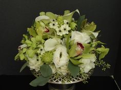 Green cymbidium and dendrobium orchids, coupled with white hydrangea, lisianthus, Star of Bethlehem and calla lilies, and green hypericum berries and seeded eucalyptus.