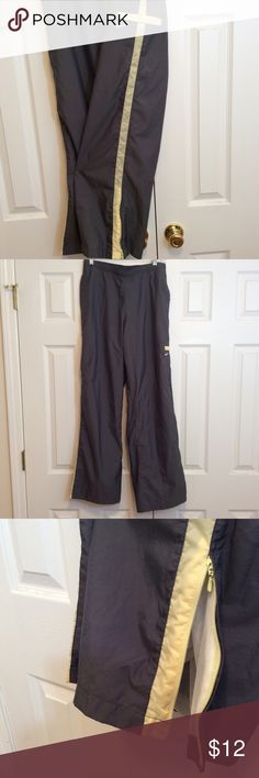 """Nike nylon athletic pants size L Nike nylon athletic pants size L.  Two side pockets with a zippered pocket on the leg, Gray in color with yellow stripe down both legs. Great Fathers Day gift. Inseam 32"""" waist 30-32 pants have elastic in the back.GUC questions???please ask Nike Pants Track Pants & Joggers"""