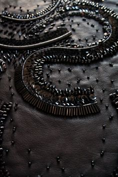 Beaded embellishment on black leather with curved patterns & mixed textures - modern embroidery; fabric design // Macadomia