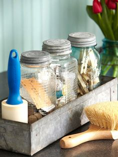 Catch Clutter - Lidded glass jars provide homes for clothespins, orphan items discovered in pockets, and sewing notions for quick garment repairs. A shallow galvanized bin unifies a mix of vintage and new containers.