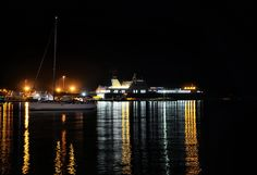 cesme port with anchored sail boat and Ro-Ro ship at night