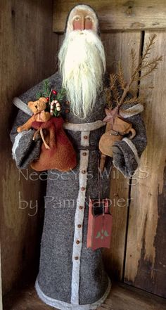 Merry Folkart, Primitive Christmas all year with this Germsn Style Santa. Standing 21 inches tall with a wooden 5 inch base, this country Santa is sure to please. The Santa has a sculptured nose, painted brown eyes, and rosy checks. His hands are made from clay and painted.The hair, beard and mustache are from lambs wool. .......hair being needle fell ted on. His coat and hood are made of a nice wool and the trim is a light gray. He has a hood and a cape around his shoulders. Rusty bells are…