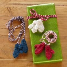 """MITTENS ON A STRING, SET OF 3--On a gift, on the tree, wrapped about a wine bottle—tiny mittens, hand knit of wool and strung upon twisted yarn. Imported. Exclusive. Set of 3. 1/2""""W x 2""""L, 7 1/2"""" string."""