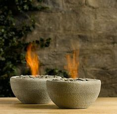 Fire bowls for the deck and patio. - 31 minute project    You'll need:    Sakrete Quickset Concrete  a bunch of rocks (perhaps dug up from your yard)  a plastic bowl  a large canned good  chafing dish gel fuel pack  PAM cooking spray  newspaper  plastic tub for mixing concrete  stick to stir concrete