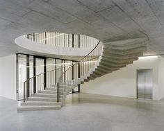 Cylindrical headquarters for motorcycling federation in Mies features dramatic sweeping staircase