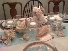 For a summer table, use shells, and floating candles in glass hurricanes.  combine blue and tan for a beachy look