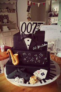 James Bond inspired cake with some of the birthday boys interests as well including saxophone and keyboards. All chocolate cake with chocolate ganache filling :-D   Www.Facebook.com/joscakeshudds | by Jo's Cakes