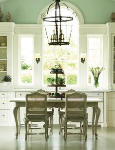 In this farmhouse-style kitchen, ceilings are a soaring 16 feet high. A large table in the center of the room can seat up to six, or be used as an island for additional workspace. Painted floors and p