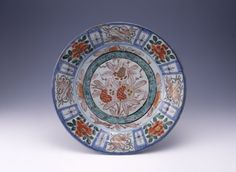 Dish. Pomegranate roundel and flower panels. Made of blue underglaze and red, gold, green, aubergine enamelled ceramic, porcelain.