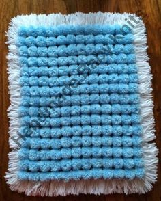 Blue pom pom blanket with white base and tassles.