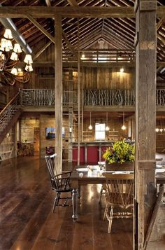 A converted German-style bank barn in Ohio is made into an elegant home with re-purposed wood floors, exposed beams, and custom-designed iron railing on the stairs  (via dining room - cleveland - by Blackburn Architects, PC)
