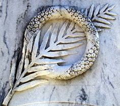 The palm frond, shown through the wreath above, may be seen as a symbol of victory. This is how the Romans used them. Christians adapted them to symbolize an individual's triumph over death.