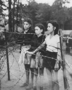 "Jewish children, forcibly removed by British soldiers from the ship ""Exodus 1947,"" stand behind a barbed-wire fence. Photograph taken by Henry Ries. Poppendorf displaced persons camp, Germany, September 1947."