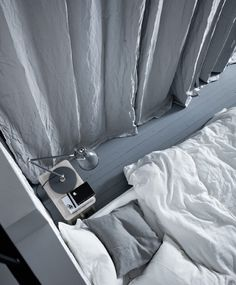 A shot from above of a bed, bedside table, and a curtain dran to hide the wall storing workout equipment.