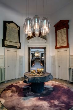 A cluster of Tom Dixon's Fade Chrome Pendant illuminates Tom Dixon's decorative Bone and Bash bowls in the hallway of the 18th century church at Clerkenwell Design Week