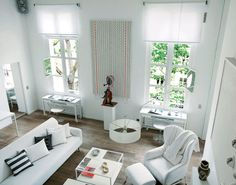 All white walls & ceiling in great room. Hardwood floors + fireplace + stair bannisters. Stained glass windows.