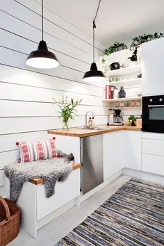 A simple and effortless scandinavian kitchen design via Erik Olsson 2/3 - the design of this is pretty straight forward with an L shaped layout and a island in the middle of the room. I love all those little details that spice up the decor, like the wide white boards that cover the walls, the small cozy bench as part of the cabinetry and the twin pendant lights over the sink.