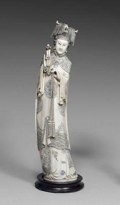 Statuette en ivoire à patine jaune, de jeune femme debout vêtue d'une robe richement décorée tenant dans sa main droite un ruyi. Sa coiffe décorée d'un phénix.  Au revers de la base, la marque apocryphe de Qianlong.  Chine, début XXe siècle