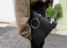 Give your outfit an edgy feel when you finish it with this Gold Ring Motif Synthetic Leather Clutch.