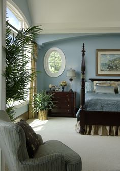 A beautiful and sophisticated masted bedroom with dark hardwood furniture and gold curtains around the large windows. Click to see how much it costs to clean your windows.