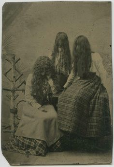 Three ladies covering their faces with hair. Tintype, Mids 1890s