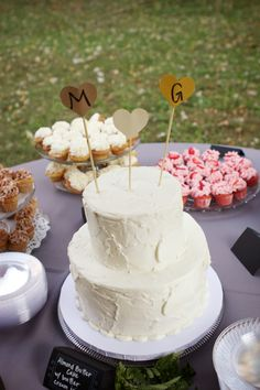 Sweet, simple wedding cake with cupcakes instead of sheet cakes. S- like the simplicity and texture of the tiers would like a pop of color or something though