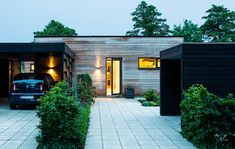 The wooden facade is both earthy and modern while the black garage creates a nice contrast. Side Hinged Garage Doors, Wooden Garage Doors, Wooden Facade, Garage Door Styles, Garage Door Design, Sectional Garage Doors, Modern Garage, Grand Homes, Villa Design