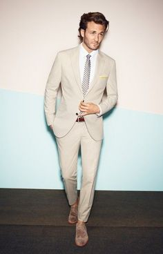cream colored suit with a polka dot tie and light brown suede boots