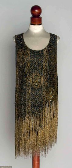 "GOLD BEADED DRESS, 1920s Black chiffon, gold geometric lattice pattern, bottom hem tiered w/ long gold fringe, keyhole back, B 36"", H 34"", L 36"", (minor bead loss) very good."