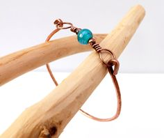 Handcrafted, lightly hammered bangle from thick pure copper wire with a coloured bead in the centre and with a hook fastening for ease of putting