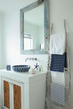 The mirror in the guest bathroom is made from Old Victorian floorboards painted blue and white. Wooden ladder towel holder. Photograph: Warren Heath, Styling: Julia Stadler