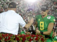 Quarterback Marcus Mariota #8 of the Oregon Ducks receives the Leishman Trophy from head coach Mark Helfrich after defeating the Florida State Seminoles 59-20 in the College Football Playoff Semifinal at the Rose Bowl Game presented by Northwestern Mutual at the Rose Bowl on January 1, 2015 in Pasadena, California.