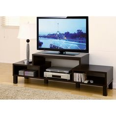 Showcase your media center with this stylish 60-inch TV console. This attractive TV stand features open shelving areas, perfect for storing movies and video games. The contemporary lines and solid legs give the stand its modern design.