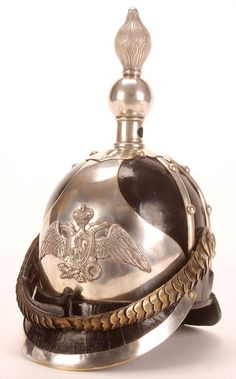AN IMPERIAL RUSSIAN PATTERN 1845 OFFICER'S HELMET OF THE ARMY'S CUIRASSIER REGIMENT. Pickelhaube type helmet with black leather body and front and back visors, the front trimmed in silvered tompak and with large silvered shaped plate, set with the Imperial Eagle, and with silvered flaming grenade finial and chinscales.