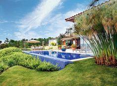 A piscina com fundo infinito é sonho de consumo de muita gente. No projeto da paisagista Paula Gabi, a caída do terreno foi disfarçada com as espécies bela-emília e íris-azul. Repare como o azul das pastilhas contrasta com o verde do jardim.