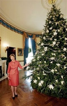 "First lady Laura Bush decorated the 2005 official White House Christmas tree with real lilies, crystal, and sparkling garlands. Her theme that year was ""All things bright and beautiful."