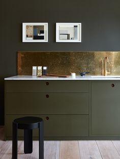 A showstopping bronze backsplash bounces light around this minimalist, hardware-free kitchen designed by Norfolk, England, design firm Naked Kitchens.