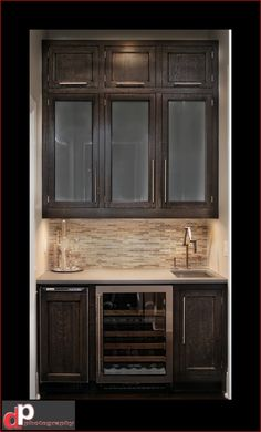 Wet Bar Showing Upper Cabinets, Backsplash, Wine Fridge, Small Sink.