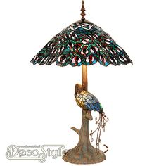 Tiffany Tafellamp Peacock  Een bijzonder mooie tafellamp. Helemaal met de hand gemaakt van echt Tiffanyglas. Dit originele glas zorgt voor de warme uitstraling. De voet is vervaardigd van bronskleurig metaal. De voet heeft de vorm van een boomstam. Hierop zit een verlichte pauw. Met 2x grote fitting (E27) Max 60 Watt en 1x kleine fitting (E14) Max 8 Watt (Pauw) Met schakelaar aan het snoer. Afmetingen: Hoogte: 49 cm Diameter Kap: 35 cm