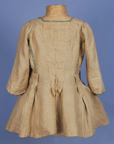 PLAID SILK PET-EN-LAIR JACKET, 18th C. Pale blue, green, cream and purple plaid having rounded front neckline squared in the back above Watteau pleats, short sleeve with bands of self ruching, neck and front trimmed with furbelows, inverted side pleats and linen lining. B-32, W-24, L-24. (Underarms torn and repaired, small splits in shoulder, stain on front trim, scattered small spots, some tearing to edge of several pleats) fair. $960.