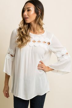 A solid hued maternity blouse featuring a semi-sheer crochet accents, long wide sleeves, a rounded neckline, and a keyhole back with button closure. This style was created to be worn before, during, and after pregnancy.