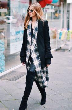 Black blazer thrown over plaid coat and over-the-knee boots.