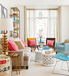 This city apartment living room looks fabulous decked out in pink, cool toned turquoise and glitzy bronze accents. Love it!