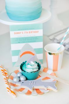 Dessert inspiration to serve at a shark themed birthday party. Shark fin cupcake, shark sugar cookie, and matching candy. White, orange, and gold paper plate and cup. Shark Party styling by Happy Wish Company. Photography by Tammy Hughes Photography. Stationery by Minted artist, Anne Holmquist. Happy Birthday Girls, First Birthday Parties, Birthday Party Themes, First Birthdays, 4th Birthday, Birthday Cakes, Shark Party, Baby Shark, Shark Fin
