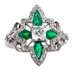 Edwardian Emerald and Diamond Ring. Loaded with eye appeal, this beautiful ring with its open quatrefoil design, centers upon an old cushion-cut diamond, framed by four radiating kite shaped emeralds, bordered by smaller round diamonds, to the scrolling shoulders and shank, mounted in platinum, approximately 12.5 mm wide overall. Circa 1910.
