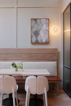 Pale wood banquettes have cushions of dark tan leather and natural linen. Ultra-warm lightbulbs cast a rosy hue on the light gray walls and oiled wood floors.