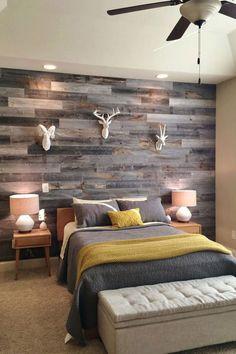 Dormitorio con muro de madera y cabezas de animales decorando, cama con cobertor gris.