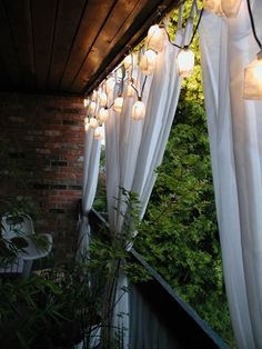 For extra balcony privacy, try hanging a simple curtain, and illuminating it with a pretty string of lights. (via Apartment Therapy)