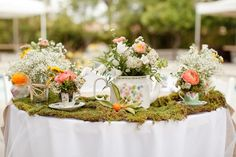 Love the contrast of the green moss with the white table cloth, baby's breath, and teapot.